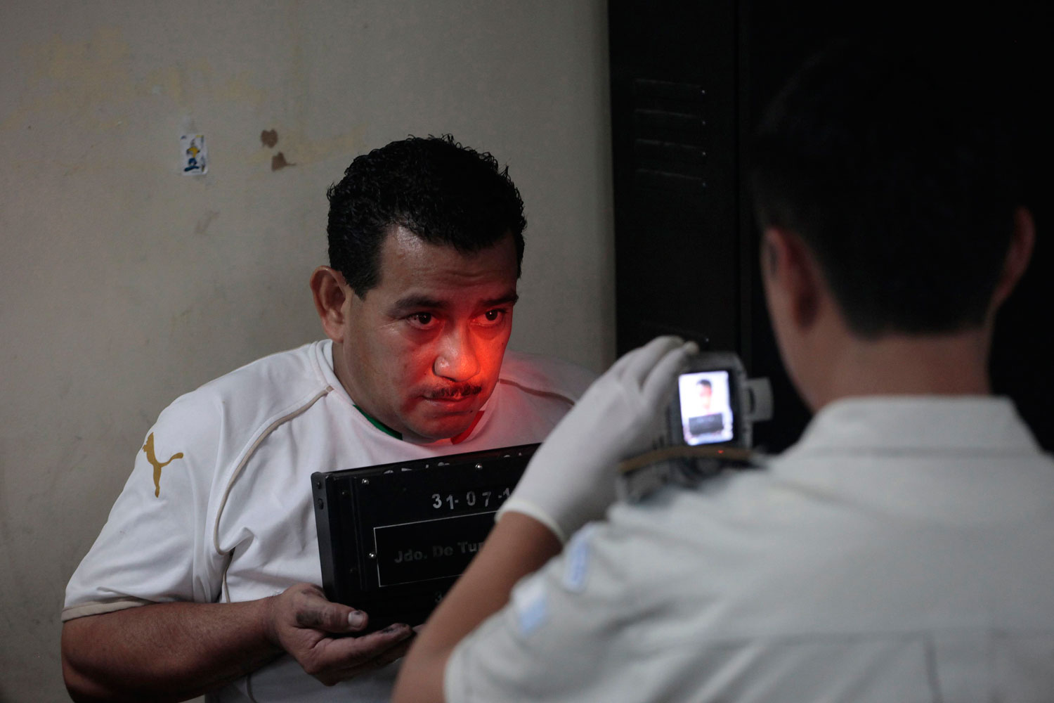 July 31, 2011. Juan Hernandez Sanchez (L), a suspect in the murder of Argentine folk singer Facundo Cabral, has his mugshot taken by the police in Guatemala City. Cabral was killed on July 9, 2011 while on the way to the airport in Guatemala City.