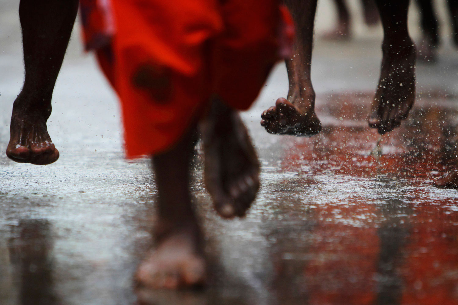 August 1, 2011. The feet of Hindu devotees are seen as they take part in a  Bol Bom  (or Say Shiva) pilgrimage in Kathmandu. The faithful, chanting the name of Lord Shiva, ran some 15 km (9 miles) barefooted to Pashupatinath temple seeking good health, wealth and happiness. Water is sprayed for them to cool down after the long distance run.