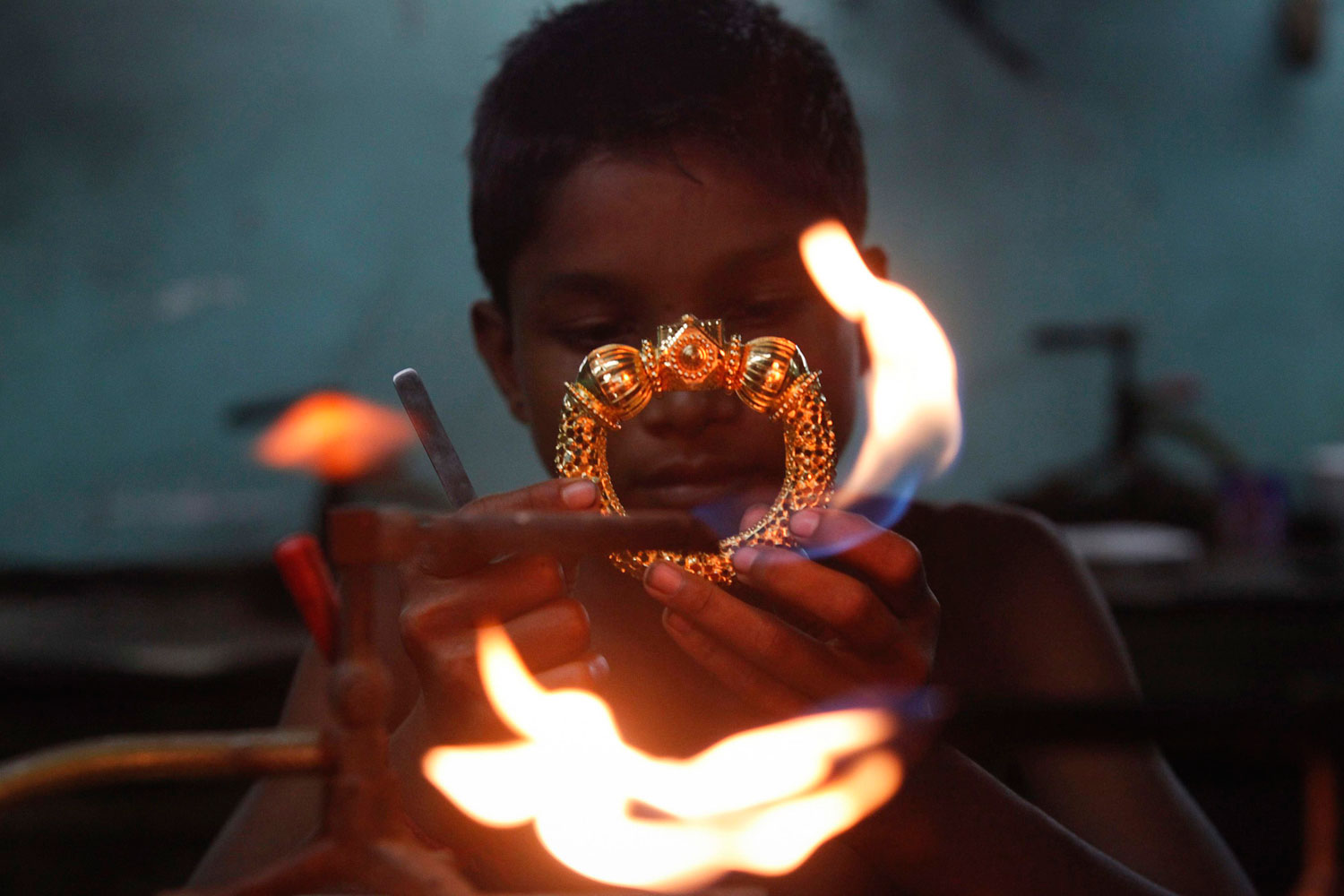 August 1, 2011. A goldsmith works on a gold bangle at a workshop in Kolkata. India gold futures fell on Monday afternoon weighed by weak overseas markets and a stronger rupee back home, though physical buyers awaited bigger falls before gearing up for festivals slated later this month, dealers said.