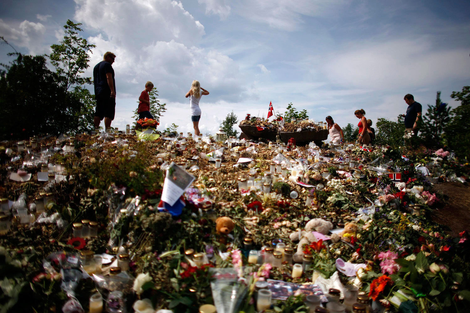 August 1, 2011. People stand on a memorial on the shore of Tyrifjorden lake overlooking Utoeya island where anti-Islam extremist Anders Behring Breivik killed 68 people in a shooting rampage in July. An opinion poll showed Norwegians believe penalties for serious crimes in their country should be tightened in the wake of the shooting and a bomb attack that killed 77 people.
