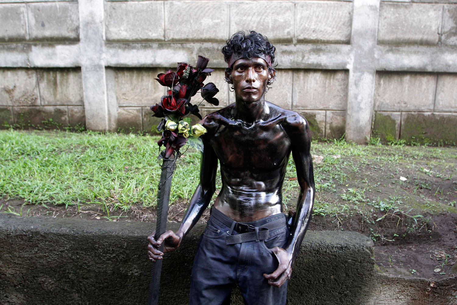 August 1, 2011. A devotee covered in motor oil takes a rest in the celebrations honoring the patron saint of Managua, Santo Domingo de Guzman, in Managua,  Nicaragua.