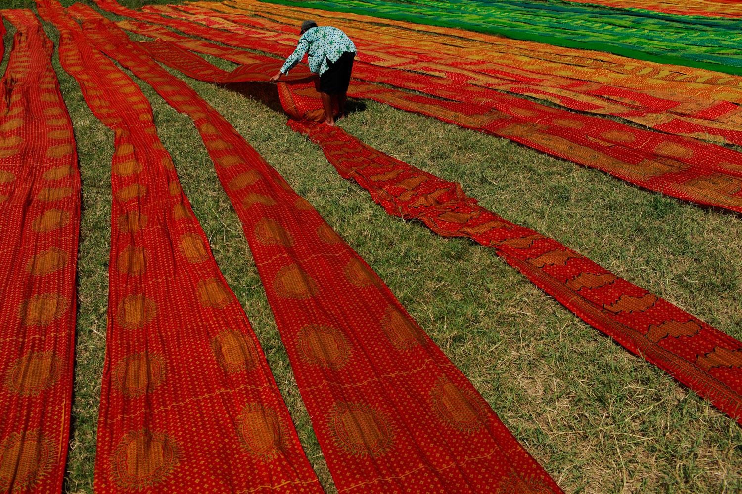 August 2, 2011. A worker lays batik cloth out on the grass to dry in Solo, central Java province. Indonesia will host the World Batik Global Summit next month in Jakarta.