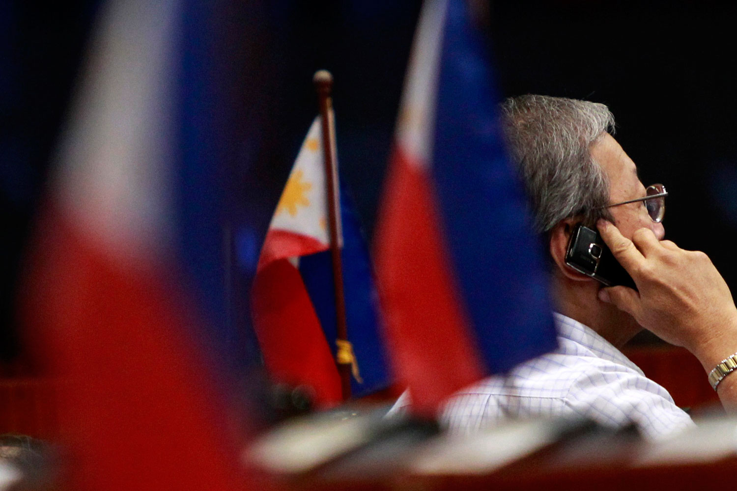 A trader talks on his mobile phone next to miniature Philippine flags during trading at the Philippine Stock Exchange in Manila's Makati financial district, August 5, 2011. The Philippine Stock Exchangeís main index fell more than 2 percent on Friday before paring losses to close down 1.4 percent. World stock markets fell for the eighth straight session on Friday to the lowest since late 2010, with more losses feared if policymakers do not come to the rescue soon to stabilise the euro zone's debt crisis and prevent the U.S. economy from sliding back into recession.