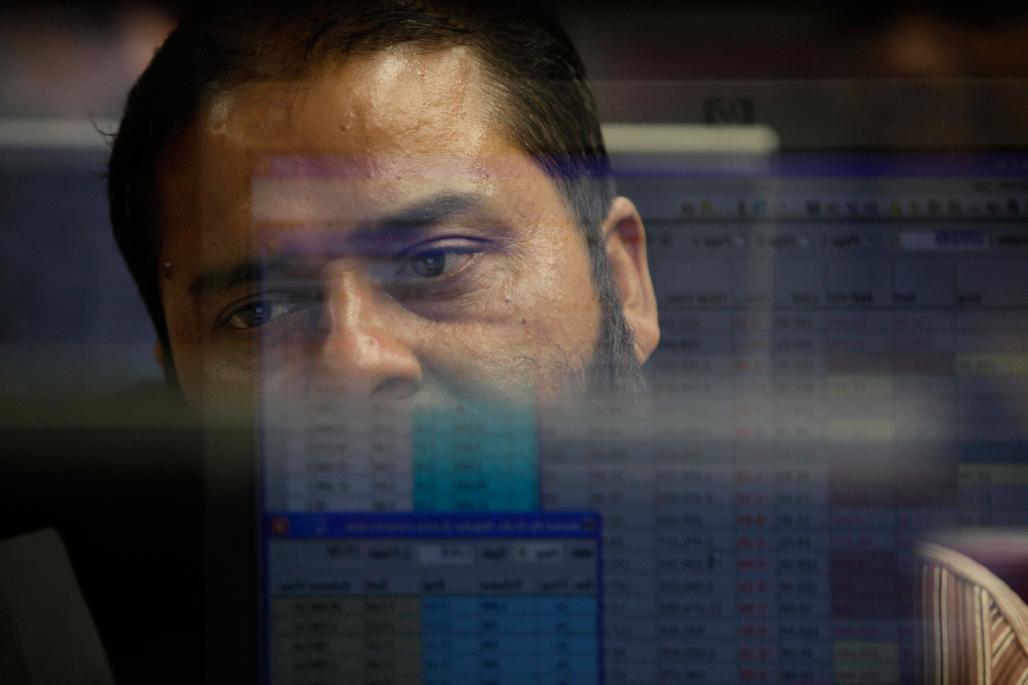 Computer screens displaying stock prices are reflected in the glass between a booth as a man monitors share prices at the Karachi Stock Exchange, August 5, 2011. Pakistani stocks provisionally ended 3.78 percent lower on Friday as foreign investors offloaded their holdings amid a global sell-off, while local investors remained cautious, dealers said.