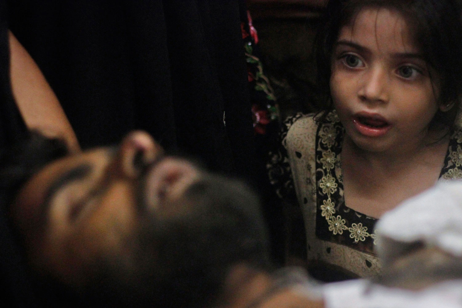 August 23, 2011. 8-year-old Sumayya, whose uncle, Imran Ali, was injured in a shootout by unidentified gunmen, looks at him as he is brought to a hospital for treatment in Karachi. Karachi faced a complete shutdown on Tuesday after the Muttahida Qaumi Movement (MQM) announced that a day of mourning would be observed against the ongoing wave of violence that has claimed nearly 100 lives in less than a week, local media reported.