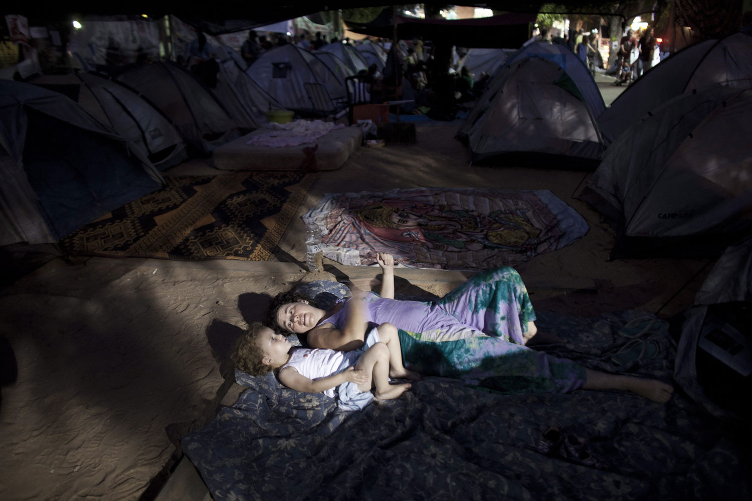 July 30, 2011. A young mother plays with her son in the tent city in Tel Aviv prior to a protest march against rising housing prices and social inequalities. Protests against skyrocketing housing prices and cost of living expenses drew an estimated 100,000 people into the streets across Israel.