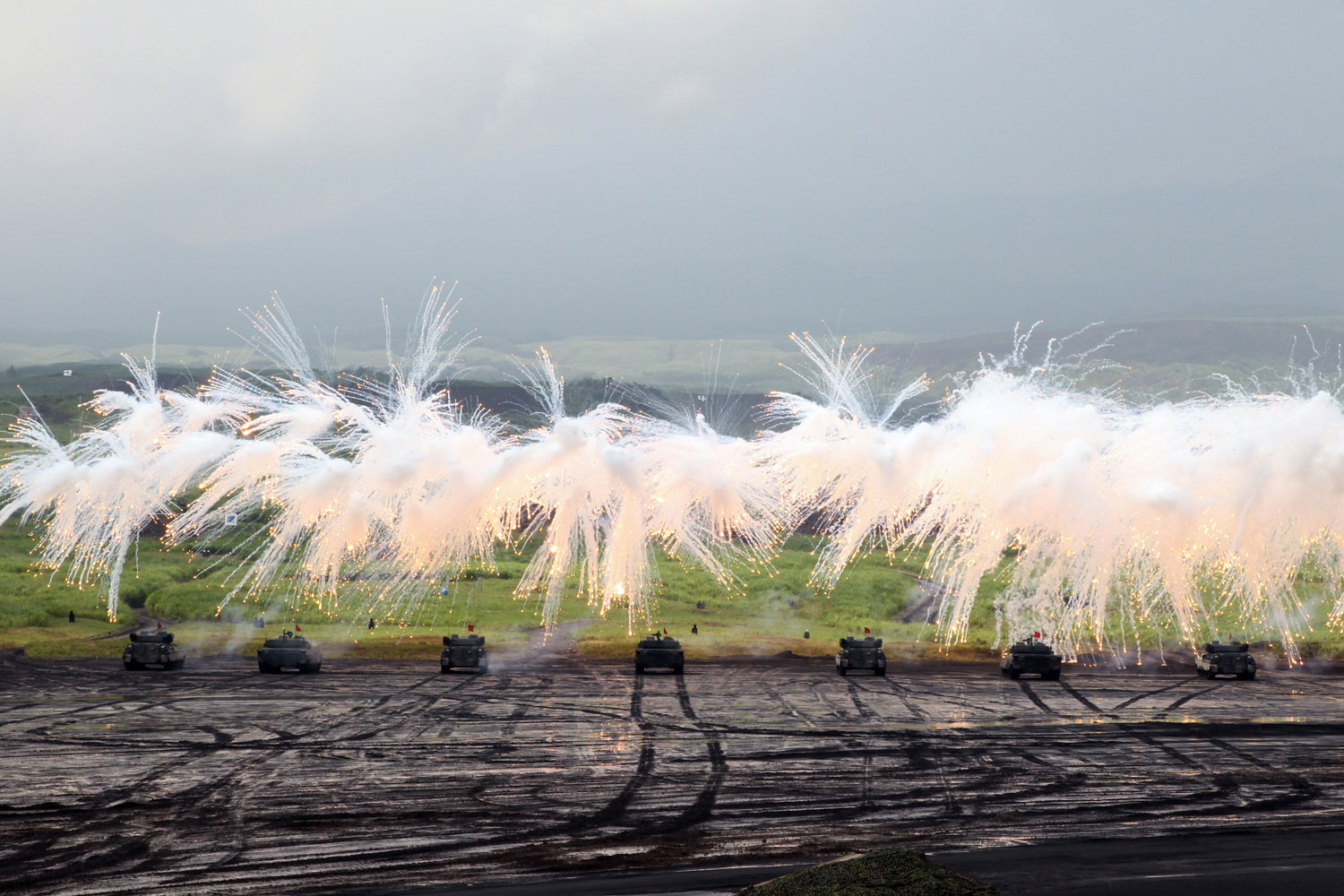 August 23, 2011. Japan Ground Self-Defense Force armed tanks fire during a fire exercise at the foot of the Mount Fuji in Gotenba, Japan. About 2,400 Ground Self-Defense personnel, 80 armed truck and tanks took part in the exercise.