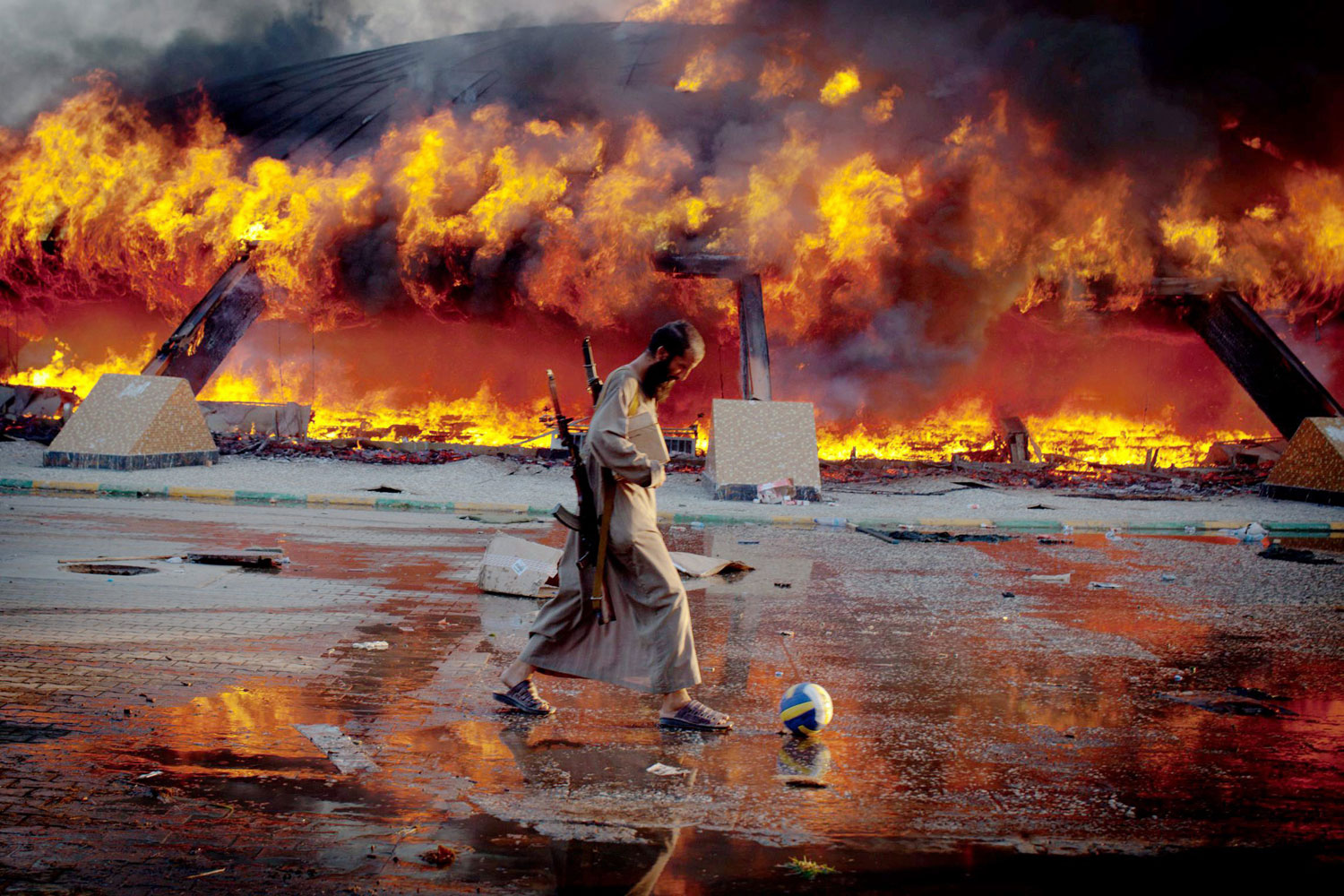 August 23, 2011. An armed rebel fighter kicks a volleyball near Gaddafi's Bab al-Aziziya compound as its engulfed in flames. Libyan rebels captured the palace after days of fighting for control of Tripoli.
