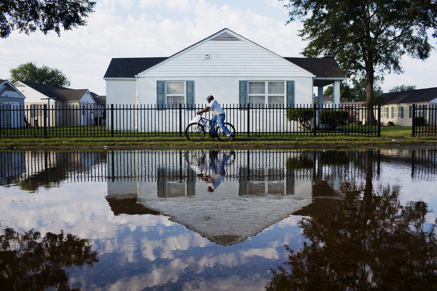 August 28, 2011, Portsmouth, Virginia. A resident rides his bicicyle past a flooded street in Portsmouth, Virginia on Sunday.