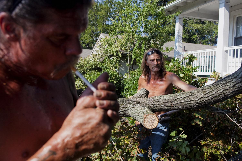 August 28, 2011, Norfolk, Virginia. Jeff Paulson lights a cigarette while Jim  LT  Emmel cuts limbs from a fallen tree on Sunday morning after Hurricane Irene.