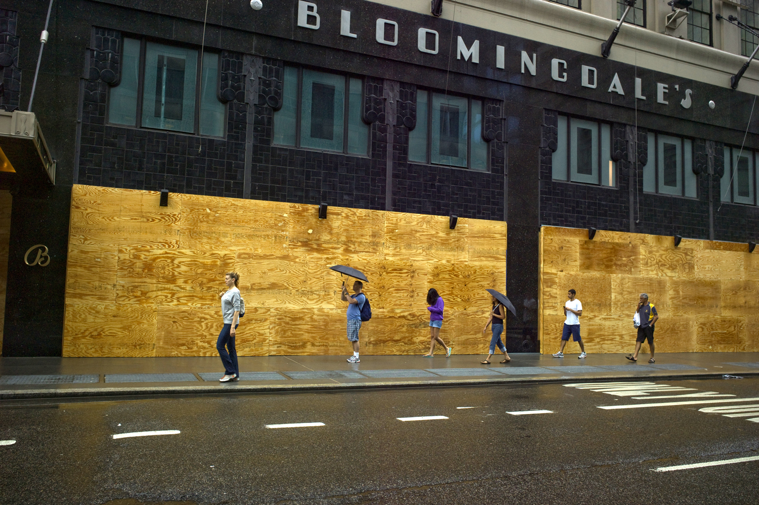August 28, 2011, New York, NY. Pedestrians stroll past a boarded up Bloomingdales on Sunday morning after the worst of the storm had passed.