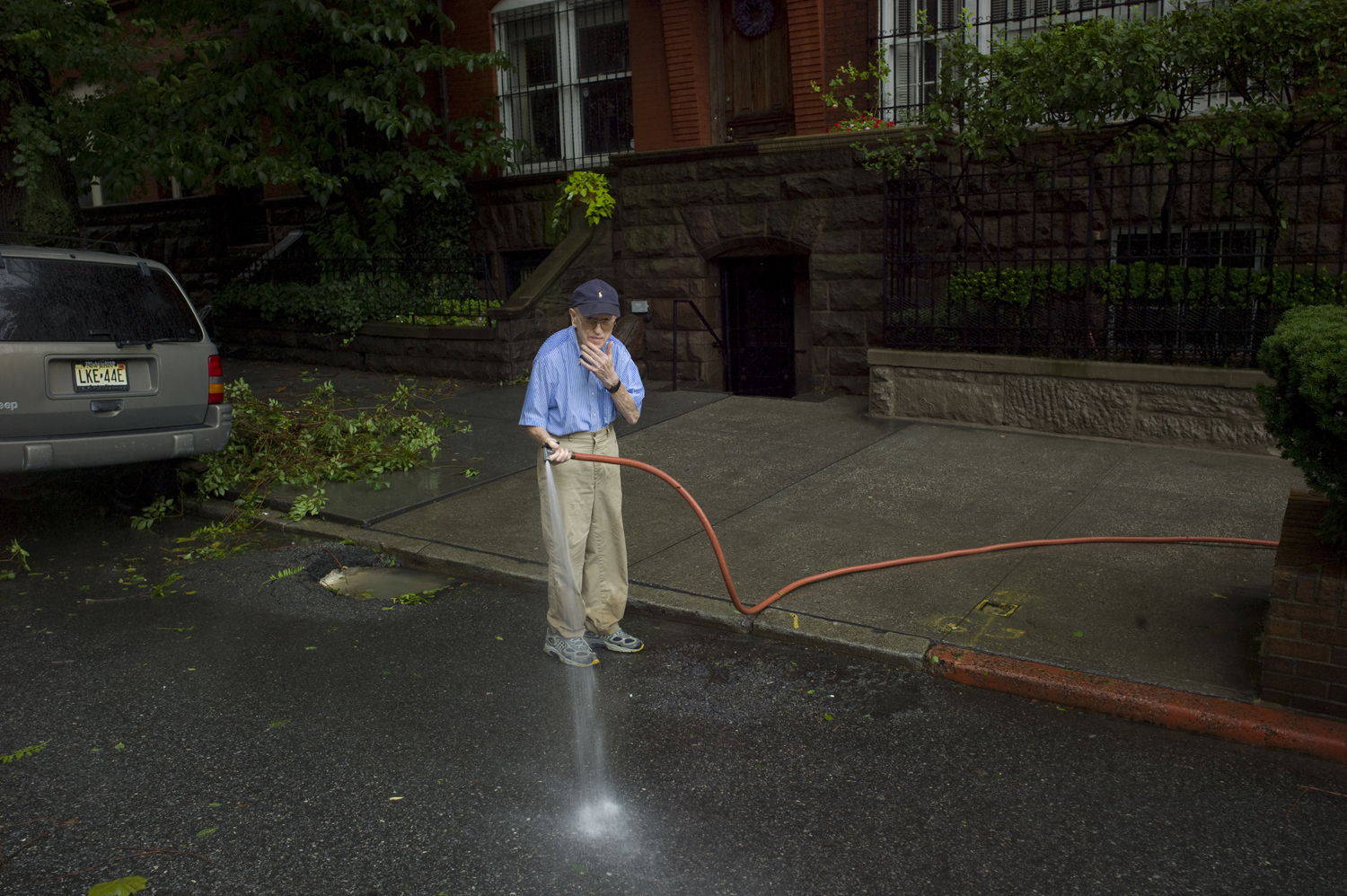 August 28, 2011, New York, NY. An elderly man cleans his sidewalk on Sunday after the storm.