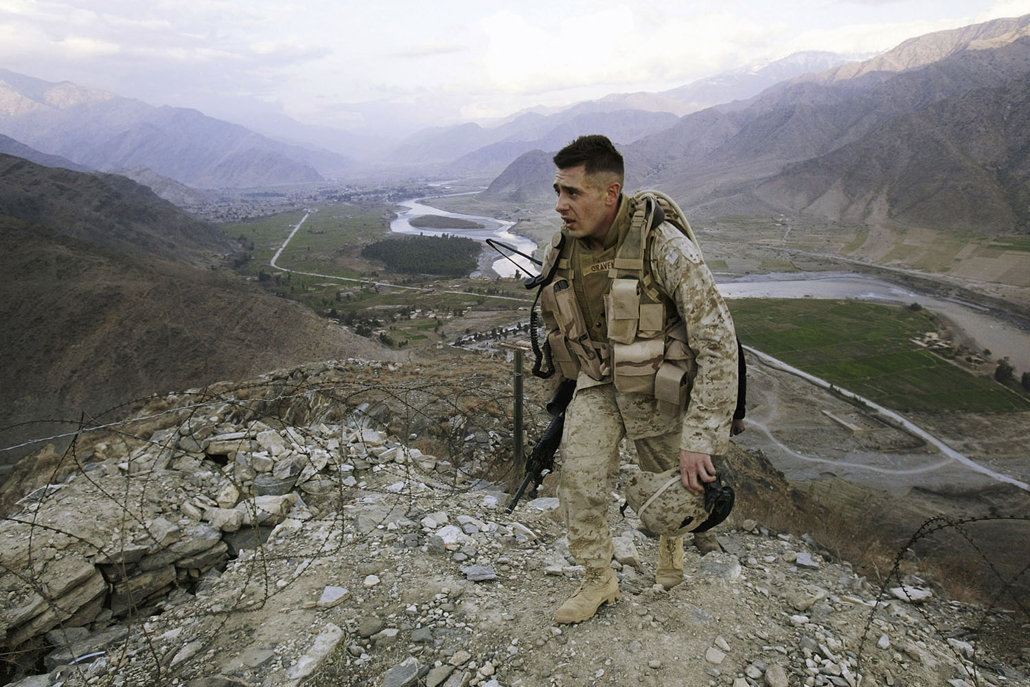 U.S. Marine Corporal Gravenese patrols in Asadabad, Kunar province, 10 kms from the Pakistan border. The Kunar River flows in the background. January, 2004