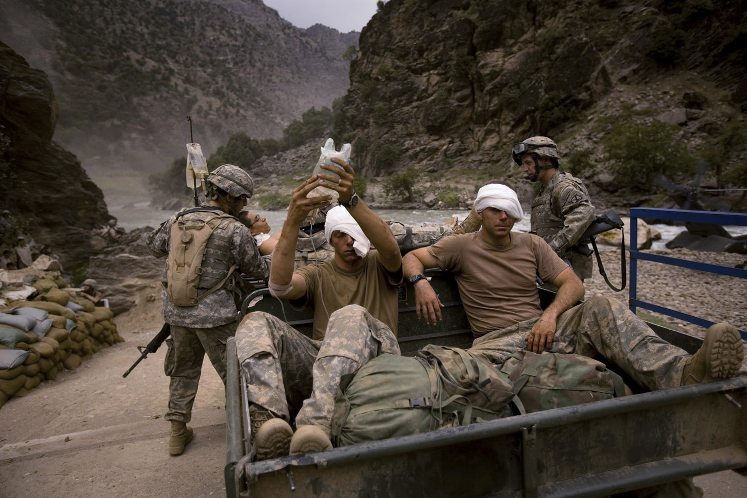 Three wounded US Army soldiers from the 10th Mountain Division who suffered shrapnel wounds to their eyes and foreheads are transported to a helicopter in Kamdesh, Nuristan. August, 2006