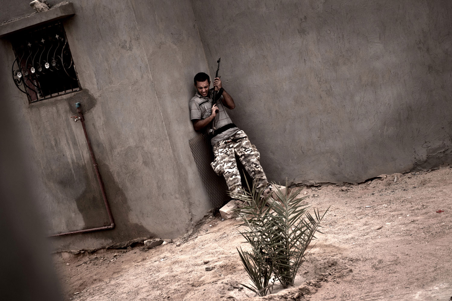 July 31, 2011. A rebel fighter takes cover during fighting in the village of Josh, at the foot of the Nafusa mountain range, in western Libya, as fighting continues between rebel forces and those loyal to the Libyan leader.  The Nafusa region has seen heavy fighting between rebels and forces loyal to leader Moammar Gaddafi since the insurgents launched a major offensive this month in a drive on the capital Tripoli.