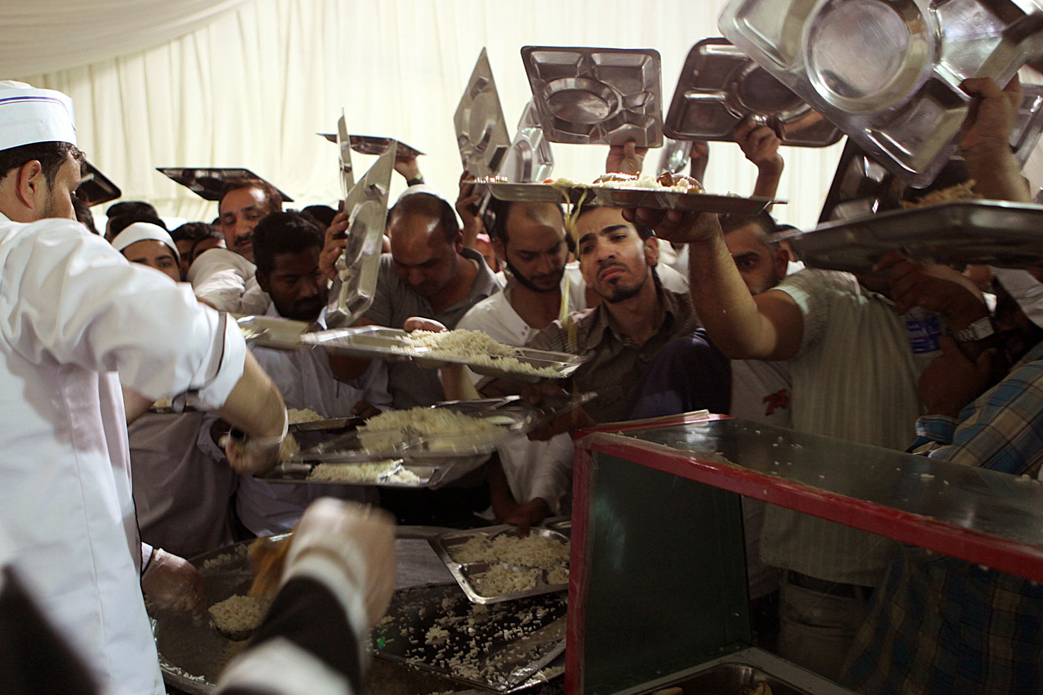 August 2, 2011. Asian and Arabs workers crowd a food distribution counter at a local mosque, as they ready to break their fast during Ramadan in Riyadh.