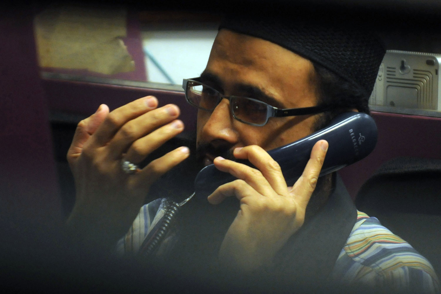 A Pakistani stockbroker talks on a phone during the trading session at the Karachi Stock Exchange (KSE) in Karachi, August 10, 2011. The benchmark KSE-100 index was 11308.99, with increase of 274.07 points in the morning session.
