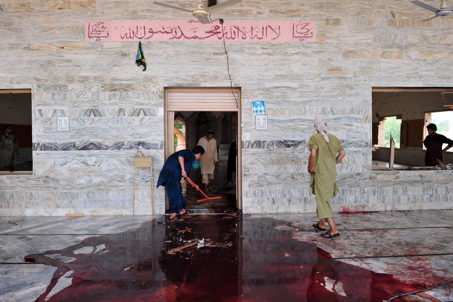 August 19, 2011. Local residents clean a mosque after a suicide bomb attack in the town of Jamrud, 25 kilometres (16 miles) from Peshawar. A suicide bomber hit a Pakistani mosque during Friday prayers, killing at least 43 people and wounding more than 100 others in the tribal district of Khyber, officials said. The Khyber bomb exploded after more than 500 people had packed into the mosque in the town of Jamrud, 25 kilometres (16 miles) from Peshawar, the main city in the northwest where most of the violence in Pakistan is concentrated.