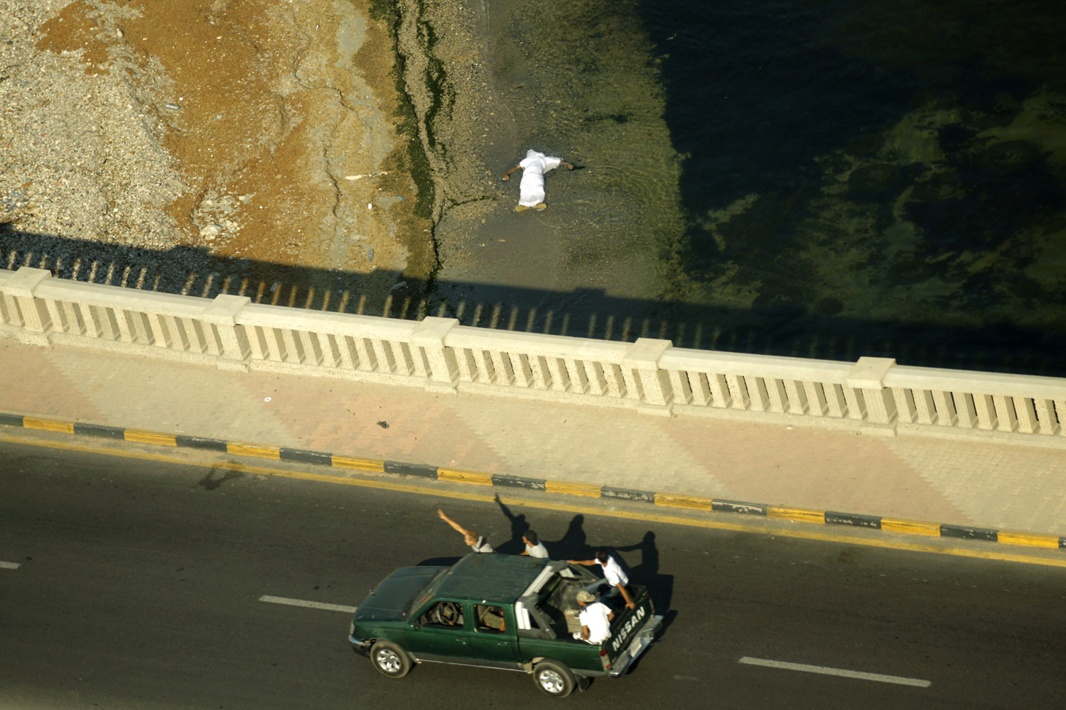 August 24, 2011. Libyan rebels patrol an area in Tripoli as a dead body floats in the sea on Fighting raged near Moamer Kadhafi's Bab al-Aziziya compound a day after it was captured by rebels, as loyalist troops staged a counteroffensive.