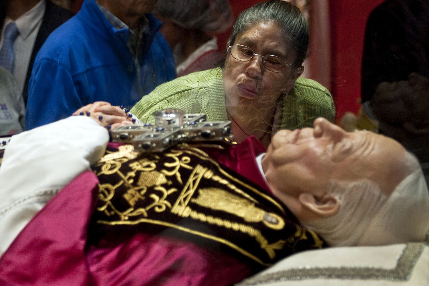 August 25, 2011. A woman kisses the glass box carrying the relics of former Pope John Paul II during a Mass at the Basilica of Guadalupe, in Mexico City. The relics will be in Mexico City for four days.