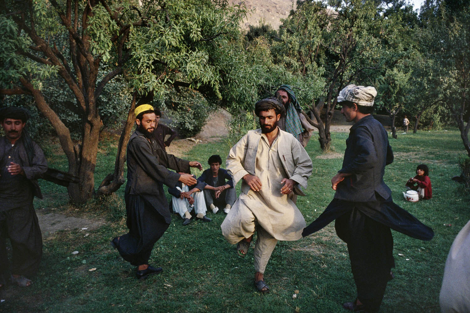 Afghan men in Kabul's Babur Gardens perform an attan dance, a traditional dance, during a Friday picnic. September, 1991