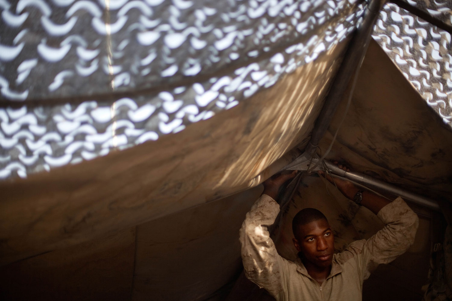 July 30, 2011. U.S. Marine Sgt. Myron Ellis, 26, of Sacramento, Calif., with the 2nd Battalion 12th Marines based in Kaneohe Bay, Hawaii, looks out from under a tent at a mountain top outpost called The Shrine Saturday, in Kajaki, Helmand province, Afghanistan.