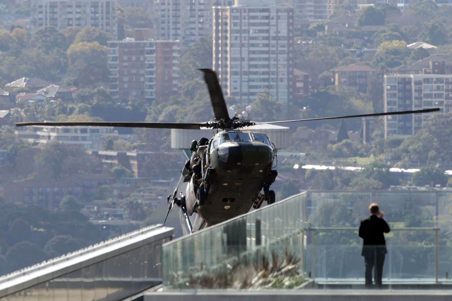 August 24, 2011. A man watches an Australian Army Blackhawk popping up between buildings during counter terrorism exercises over the Central Business District in Sydney, Australia, Wednesday.