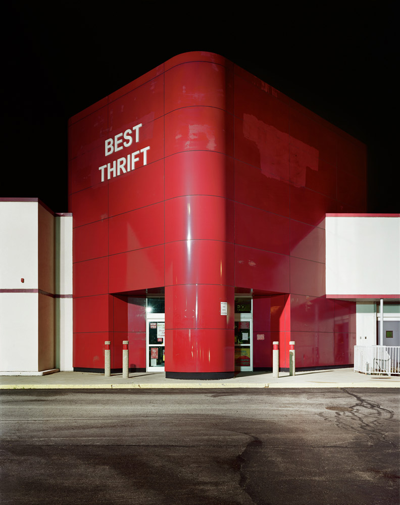 Best Thrift, 2010                                In May of 2008 I made a photograph of an empty Circuit City. A month or so later they were all gone. Most of retail spaces are only really designed with the entrance in mind. The Circuit City stores are meant to mimic a large plug plugging into the earth. Commercials from that era animate the idea.                                In addition, I am fascinated that Capitalism reinvents its own rules to survive. I photographed several of these Circuit City stores, one masked in yellow, another white washed and being changed into another electronics store. This one, appropriate to my earlier work, had transformed into a thrift store.