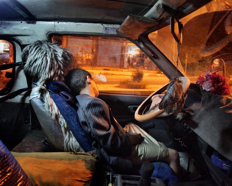 A boy sleeps inside a car in the southwestern city of Ibb, Yemen. August 2010.