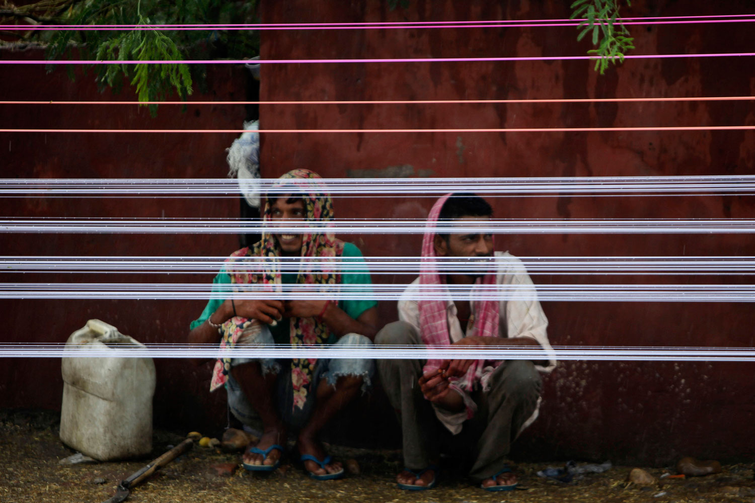 July 29, 2011. Workers take take break between coloring threads for kites under rains in Jammu, India.