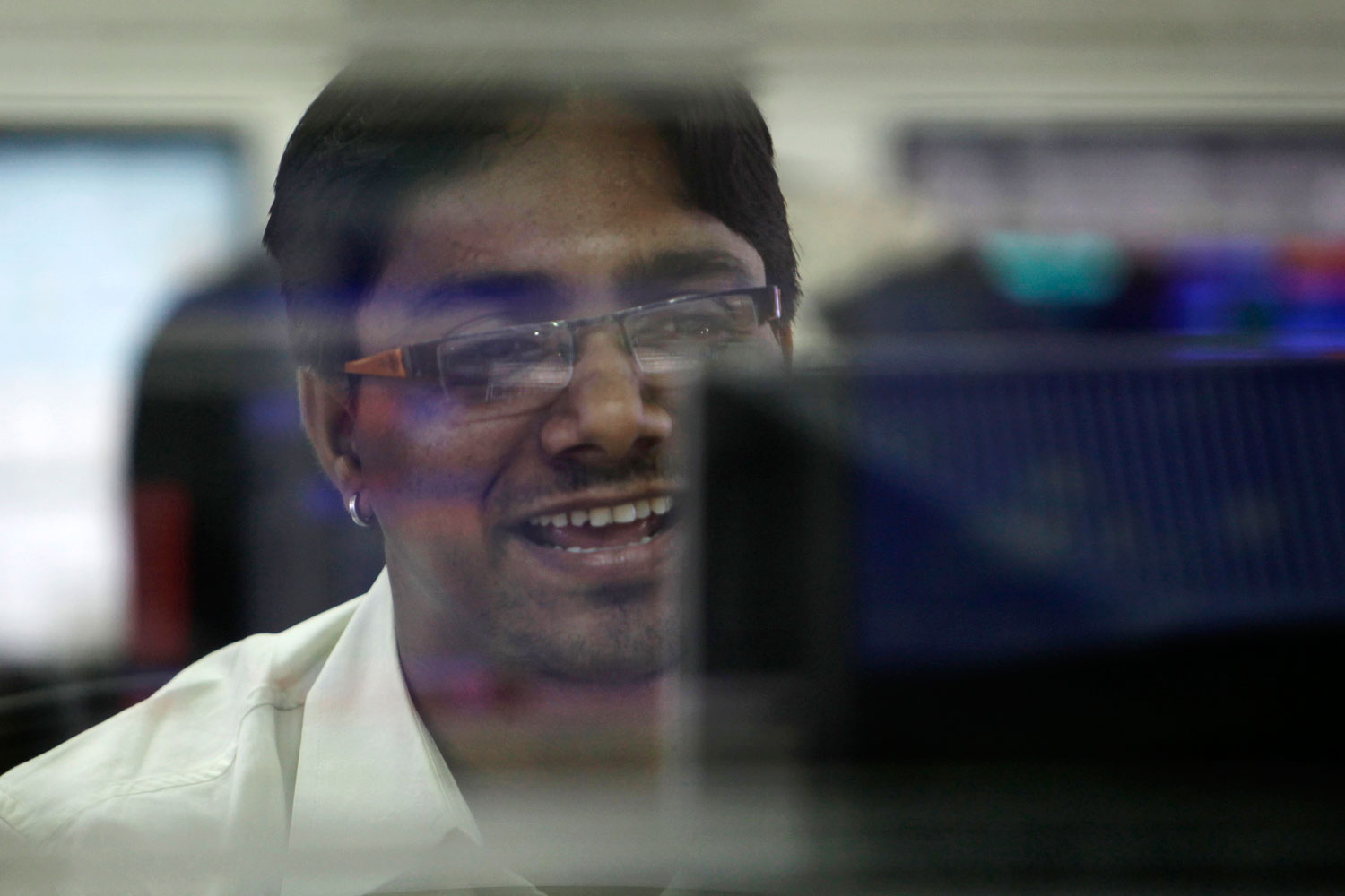 An Indian stock broker reacts as he watches the Bombay Stock Exchange (BSE) index on his trading terminals in Mumbai, India, August 10, 2011. Asian stock markets jumped Wednesday following a surge on Wall Street triggered by a Federal Reserve pledge to keep interest rates super low for the next two years to help the ailing U.S. economy.