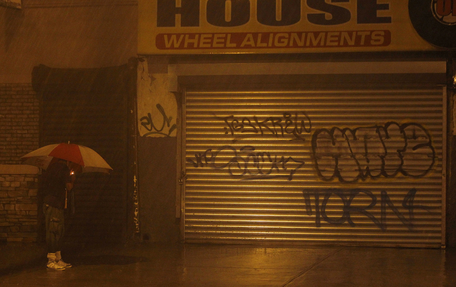 Aug. 27, 2011, Newark, New Jersey. Jose Rivera, 70, pauses on his way home from a night club on Saturday night to light a cigarette as heavy rain from incoming Hurricane Irene covers the city.