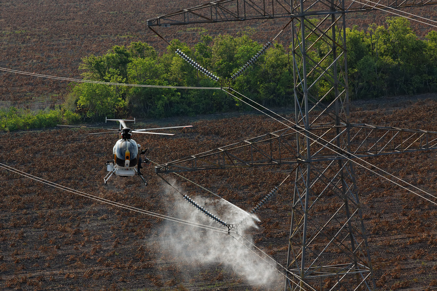 Normally rain would be enough to rinse the accumulated dust and sand from power transmission lines, preventing them from damage, but in an extreme drought, some power companies hire helicopters to hose the lines off, using tens of thousands of gallons of purified water in the process.