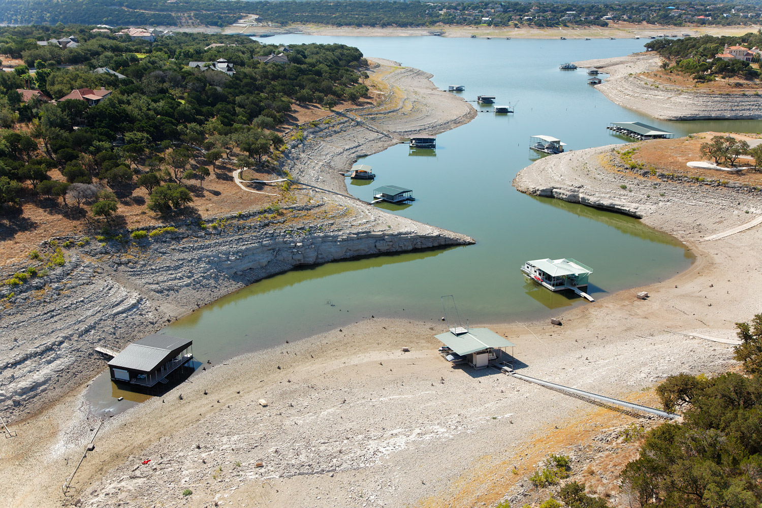 In Texas, stranded boat docks sit on a dried-up creek feeding Lake Travis, which is over 26 feet below its normal level.