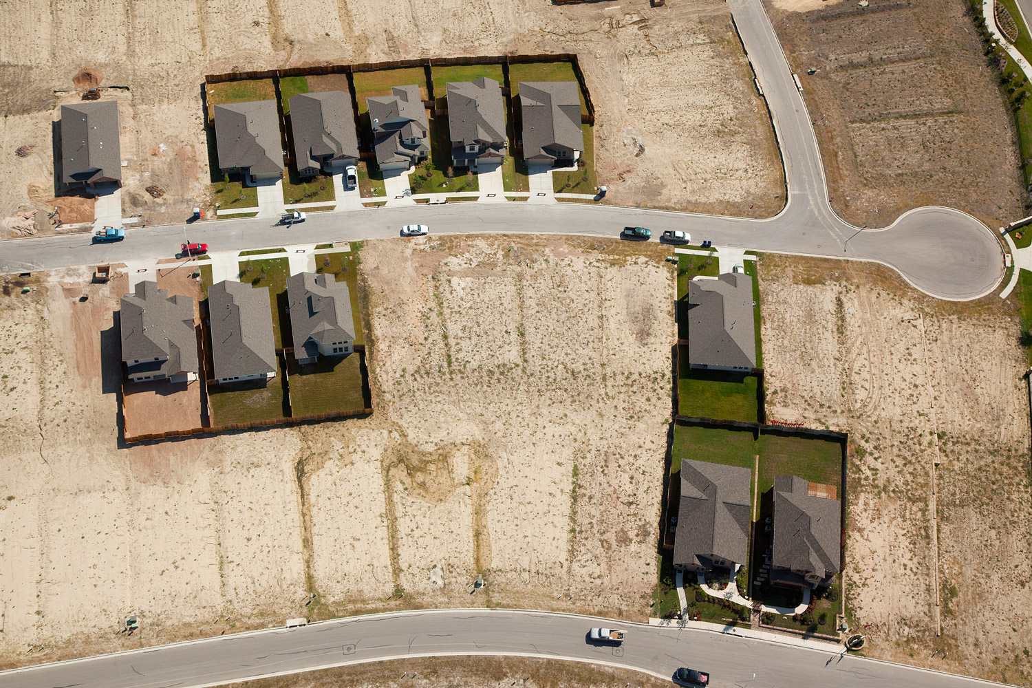 A few green lawns dot the dry landscape of this residential development located between Austin and San Antonio. Cities in the South are increasing restrictions on residential water use.