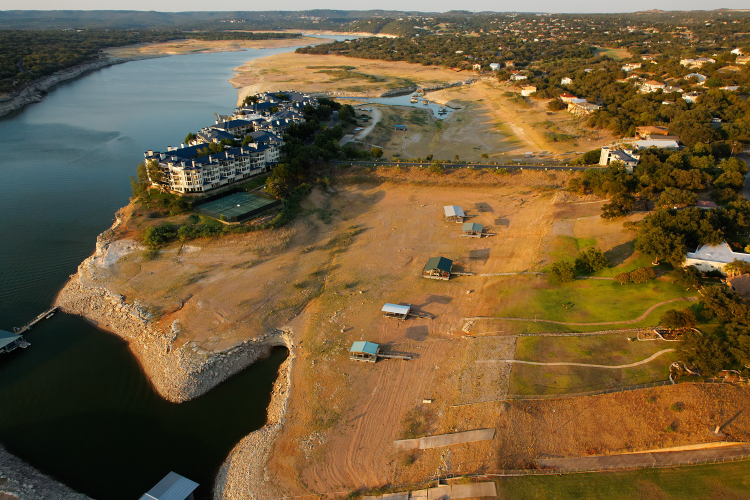 The Island,  a resort on Lake Travis, is normally a peninsula surrounded almost completely by water. The level of the Lake has dropped, and it now sits on dry land, as do the neighboring boat docks.