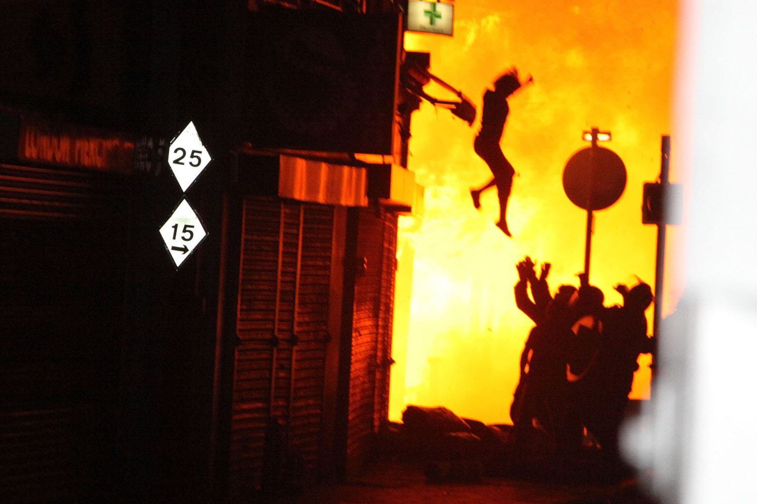 A woman is seen jumping from a burning building on Surrey Street after rioting in Croydon, England, on Aug. 8, 2011.