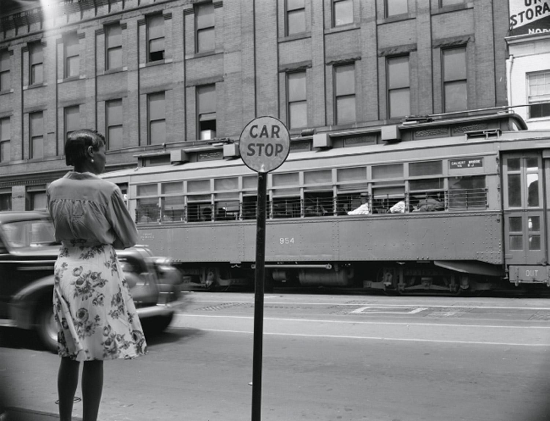 A woman stands at a Washington, D.C. street corner, August 1942.