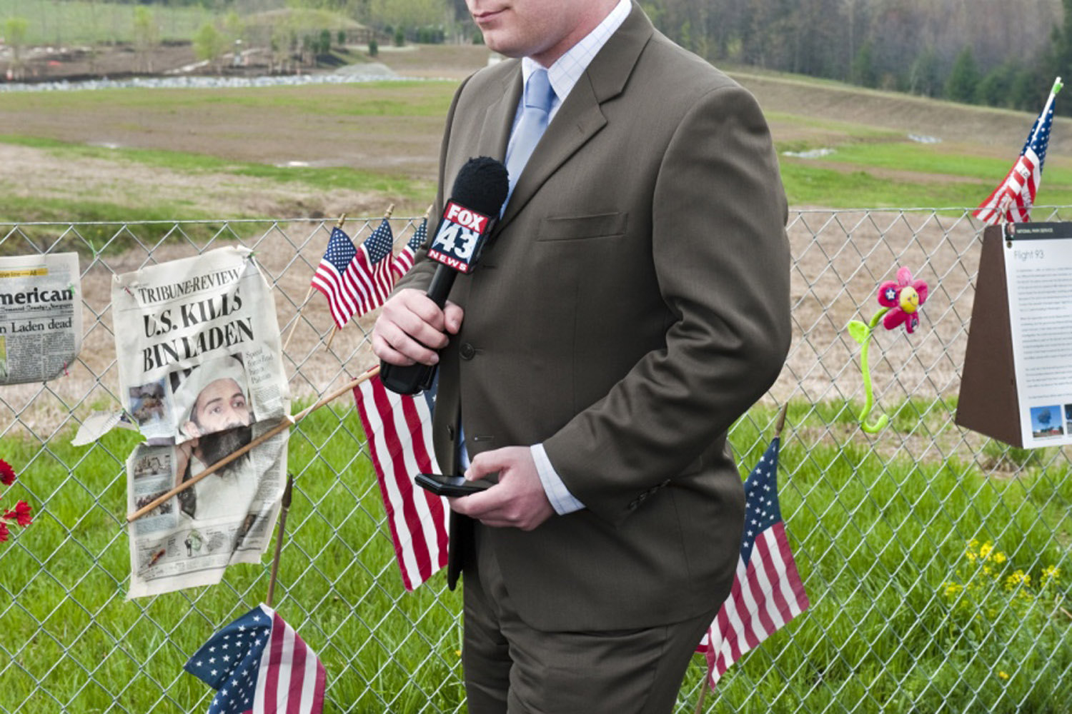 A newscaster stands in front of a fence at the crash site of Flight 93, reporting the news of Osama Bin Laden's death.