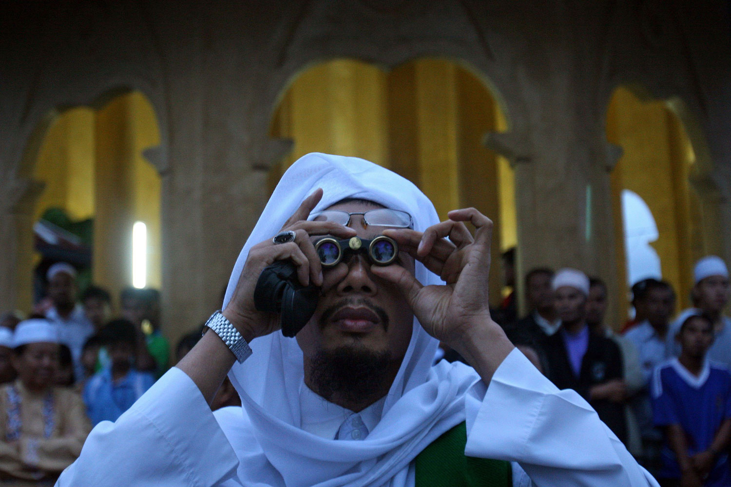 August 29, 2011. A Muslim man uses binoculars to search for the moon in Thailand's Yala province. The appearance of the new moon marks the end of fasting and spiritual cleansing during the Islamic holy month of Ramadan and the start of a three-day celebration known as 'Id al-Fitr, the Breaking of the Fast.