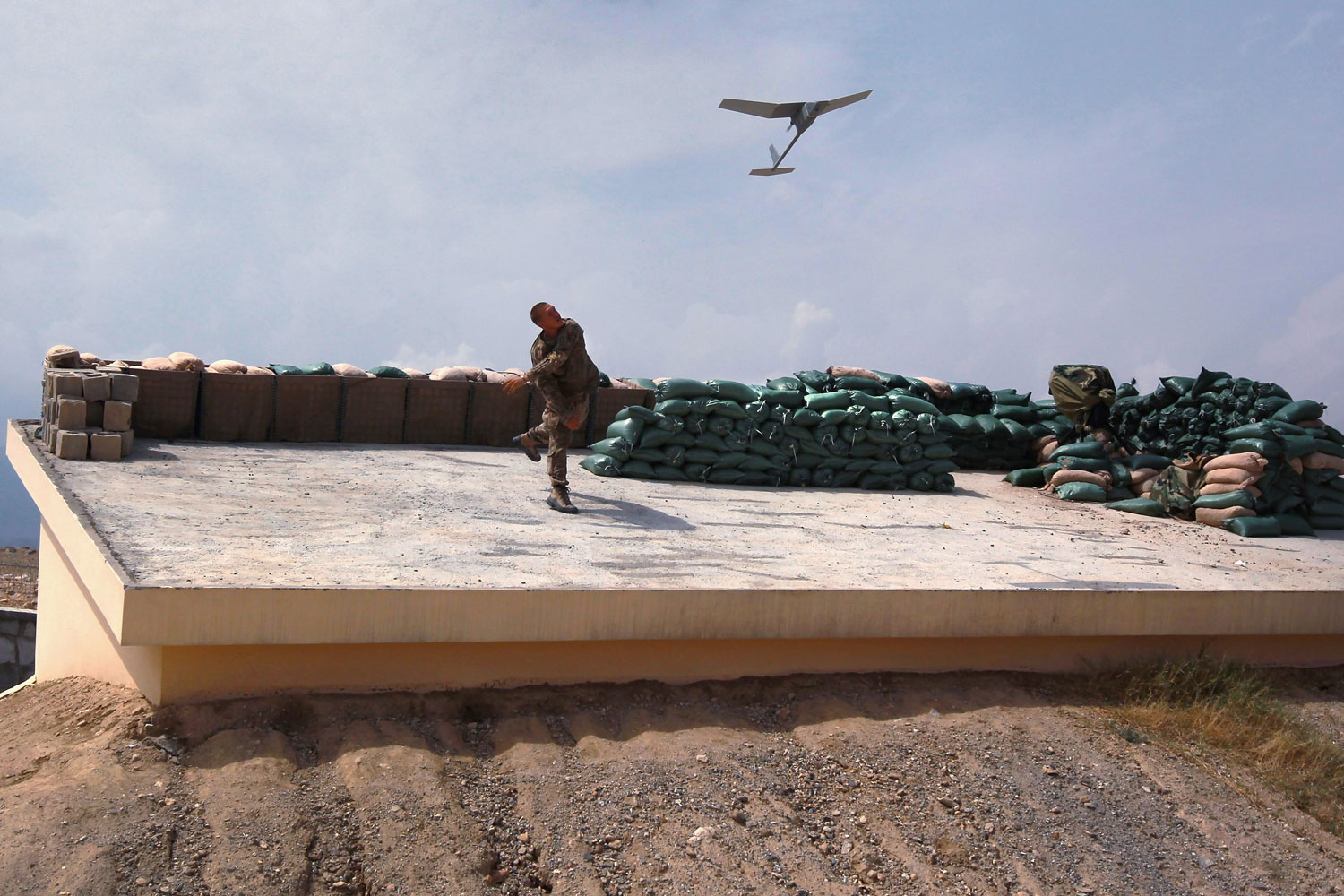 August 30, 2011. U.S. Army Sgt. Don Stolle launches a Raven surveillance drone into the air from the Afghan government district center in Achin, Afghanistan. The military uses the small unmanned aerial vehicles (UAVs) to transmit live video back and watch for possible Taliban movements near U.S. forces on the ground. The craft, controled remotely like a model airplane, can fly for up to 1 1/2 hours and a distance of about 6 miles on its electronic motor before being brought back and relaunched with a fresh battery.