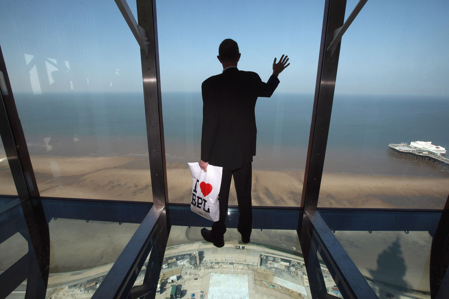 September 1, 2011. A visitor tries out the new glass Skywalk at the top of the refurbished Blackpool Tower in Blackpool, England. After a GBP £20 million refurbishment, the iconic seaside Blackpool Tower opened to the general public. The observation deck at the top of the tower becomes the Blackpool Tower Eye and features a skywalk made of glass overlooking the sea and the promenade.