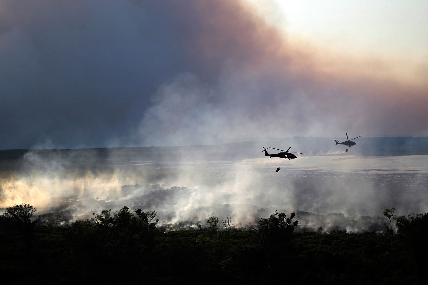 August 30, 2011. National Guard Blackhawk helicopters equipped with Bambi buckets drop water on the marsh fire in New Orleans East.