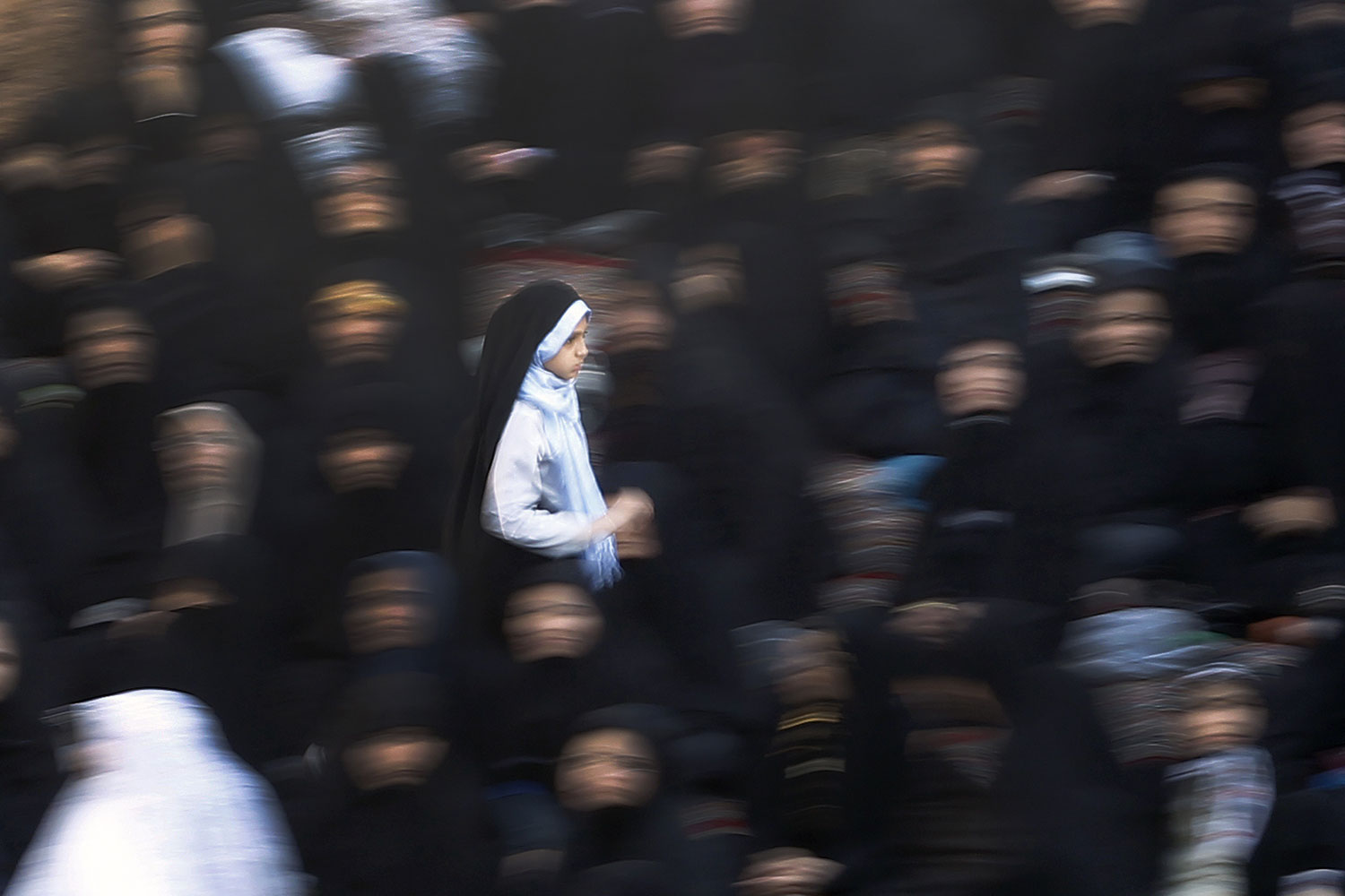 Aug 31,2011. An Iranian girl passing by the muslim worshipers at Imam zadeh Helal ebne Ali shrine in Aran o BidGol during Eid-al-Fitr festival. Aran o BidGol  is  a city in Isfahan province, located about 250 KM south of Tehran, Iran . The Eid-al-Fitr festival marks the end of the holy Muslim fasting month of Ramadan.