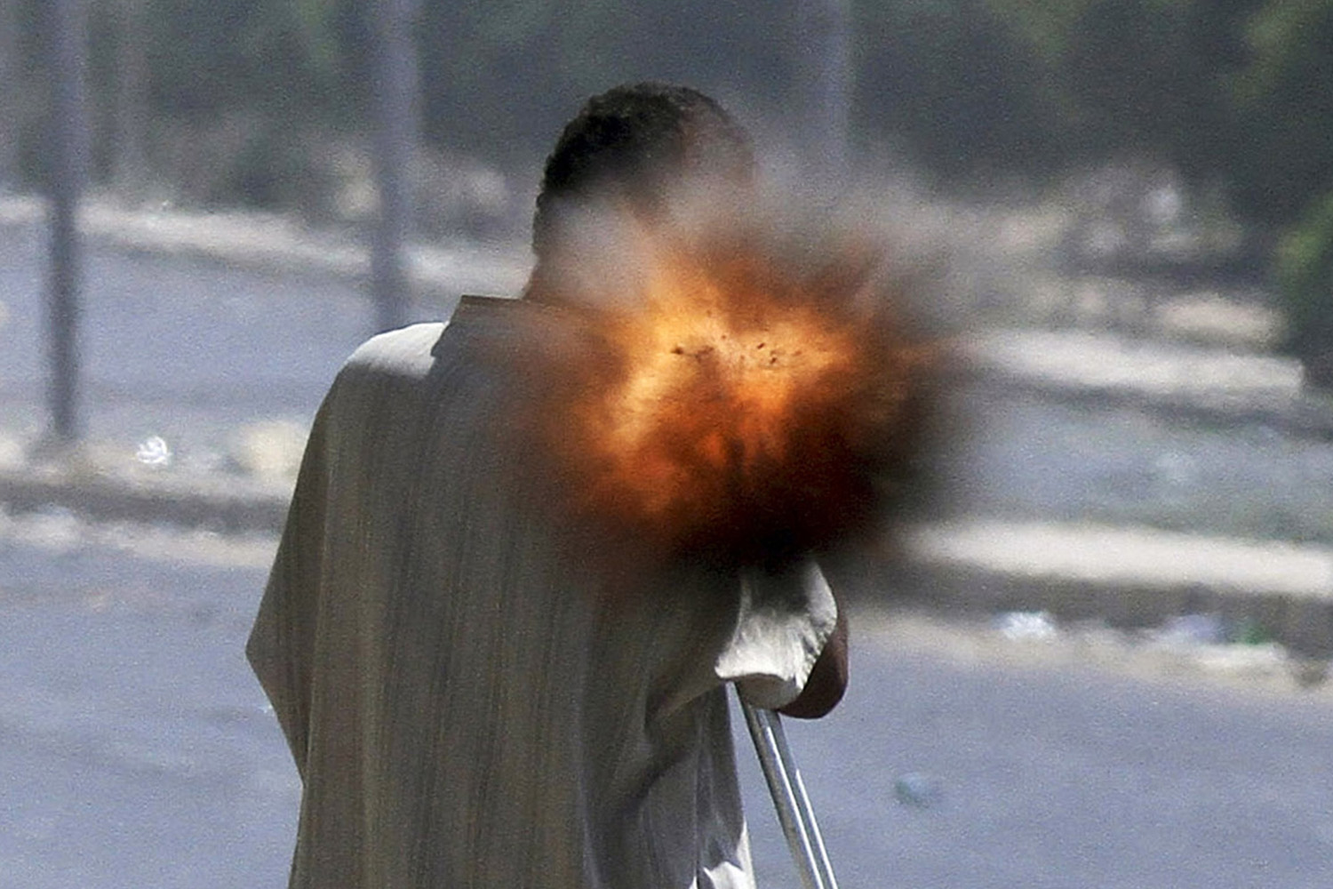 September 24, 2011. A rebel on crutches fires a rocket propelled grenade while fighting on the front line in Sirte.