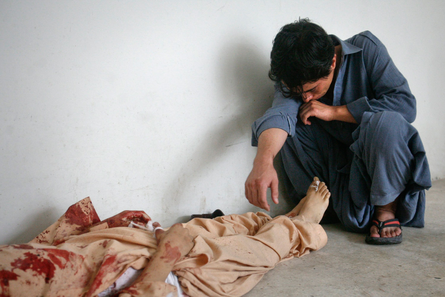 August 31, 2011. A man sits grieving next to the body of his eleven-year-old brother after his body was recovered from the site of a car bomb blast in Quetta A suspected suicide car bomb attack killed 10 people in Pakistan's southwestern Baluchistan as the country celebrated the Muslim festival of Eid al-Fitr.