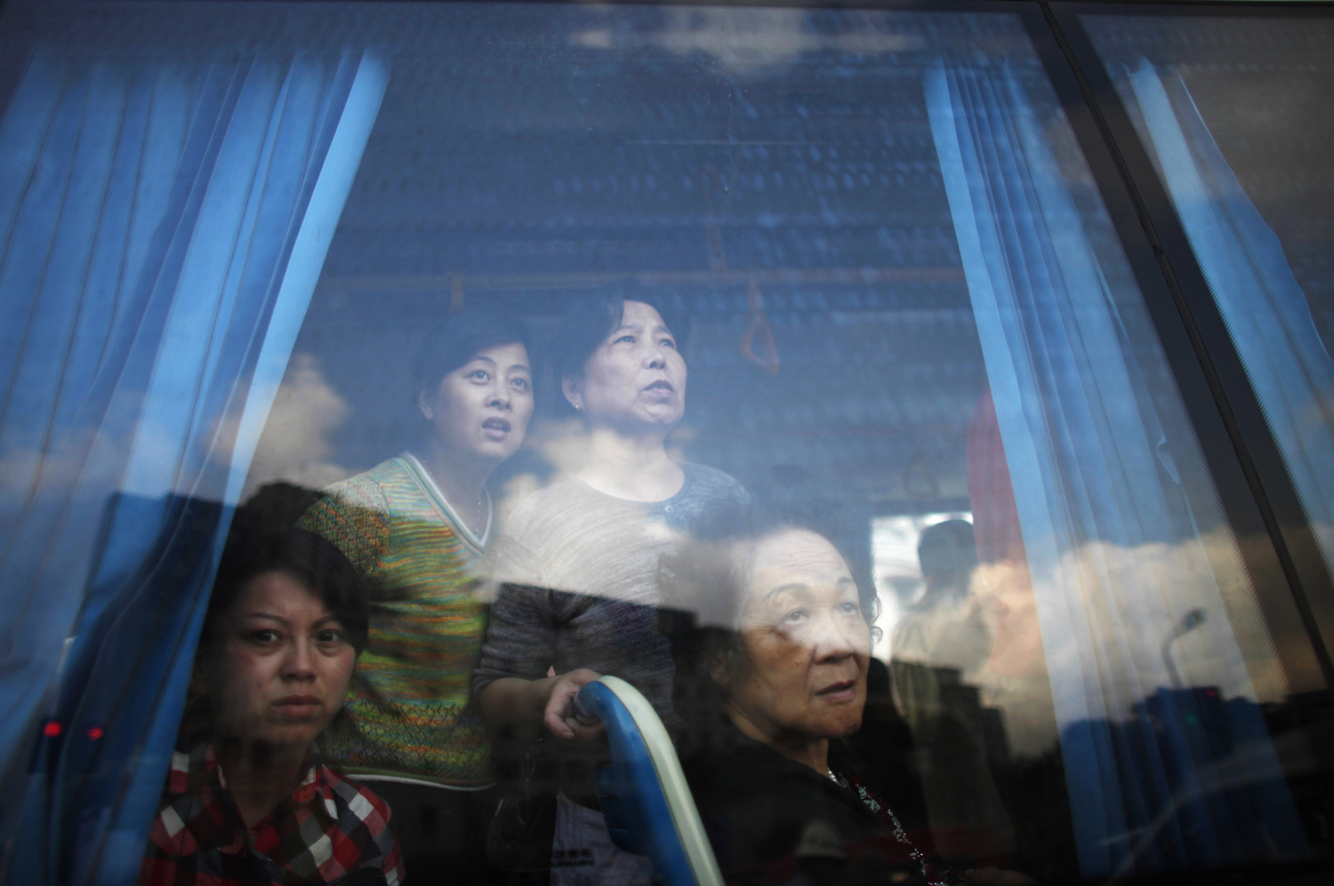September 27, 2011. People look on from inside a bus at the rescue operations taking place at Yu Yuan Garden station after a subway train collision in Shanghai. Two subway trains collided in Shanghai injuring over 200 passengers.