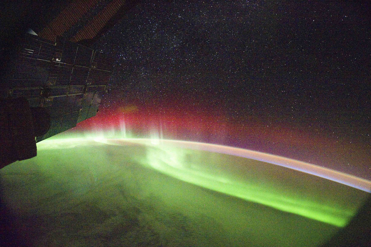 September 26, 2011. A NASA image captured from the International Space Station shows rare aurora appearing in red. The colours depend on which atoms are causing the splash of light seen in the aurora. In most cases, the light comes when a charged particle sweeps in from the solar wind and collides with an oxygen atom in Earth's atmosphere. This produces a green photon, so most auroras appear green. However, lower-energy oxygen collisions as well as collisions with nitrogen atoms can produce red photons—so sometimes aurora also show a red band as seen here.