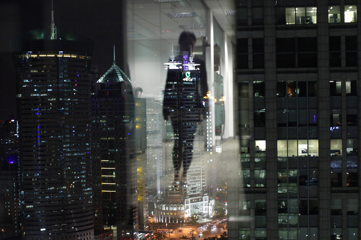 September 22, 2011. A woman is reflected in a window of an office in the financial district of Pudong in Shanghai, China.