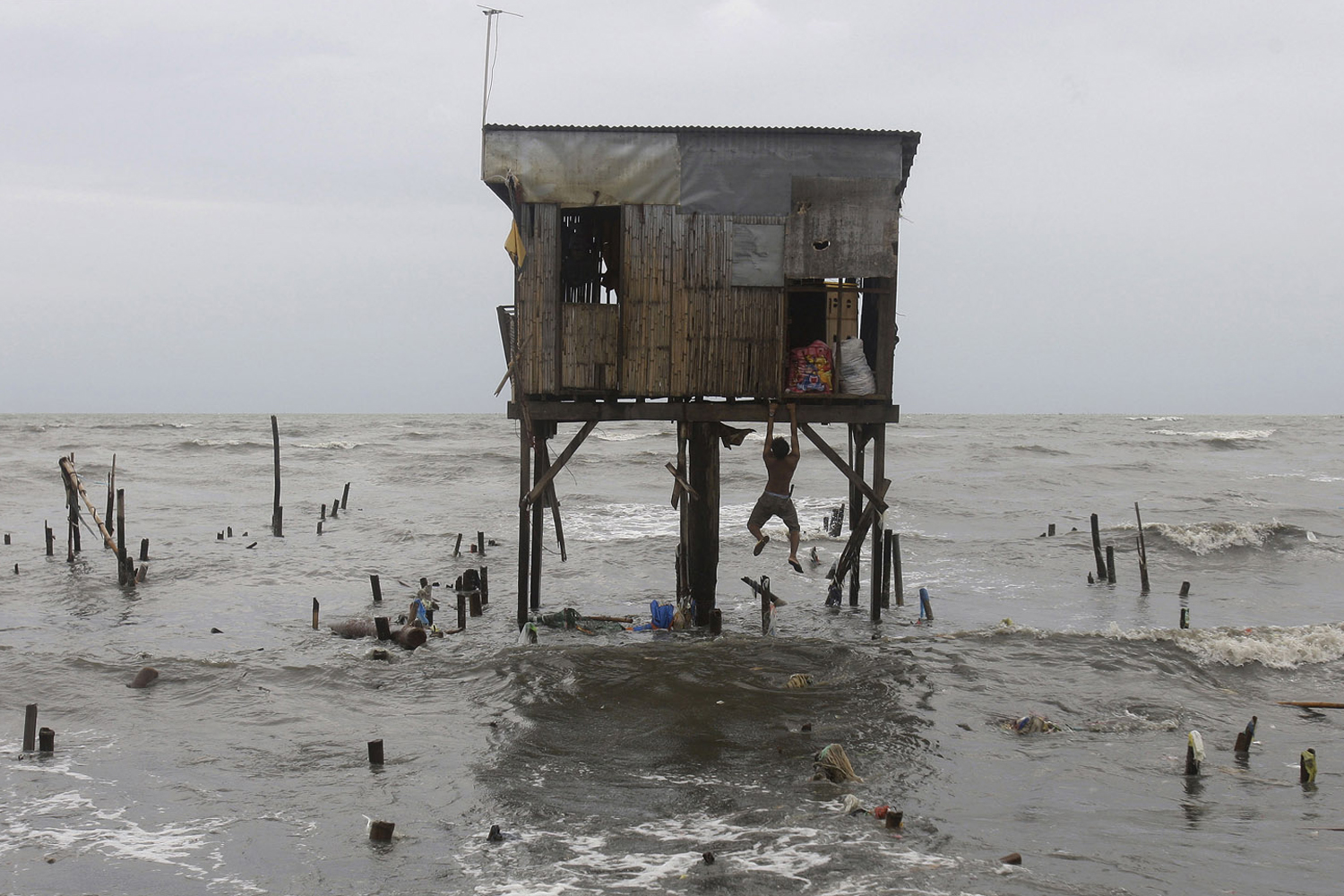 September 28, 2011. A man hangs on to what remains of a house that was built on stilts as he tries to recover belongings after Typhoon Nesat wiped out most of his neighbors' homes along a coastal village in Navotas, north of Manila, Philippines. Emergency services and residents in the Philippine capital cleaned up and restored electricity after the powerful typhoon unleashed flood waters and fierce wind that sent huge waves crashing over seawalls.